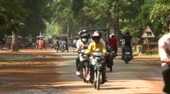 Tuk-tuks and motorcycles on a paved road Stock Footage