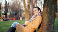 Happy woman sitting by the tree, dolly shot Stock Footage