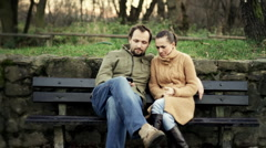 Happy couple with cellphone sitting on bench in the park Stock Footage