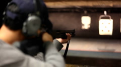A man fires a rifle at a target at an indoor shooting range. Stock Footage