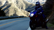 Stock Video Footage of Motorcyclist pulls out onto a winding mountain road.