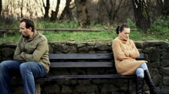 Relationship difficulties, young couple sitting on bench in the park Stock Footage