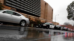 A line of police vehicles pass along a street on a rainy day. Stock Footage