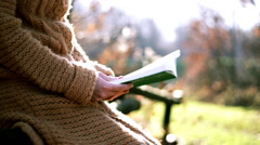 Woman sitting in the park and reading book, steadicam shot Stock Footage