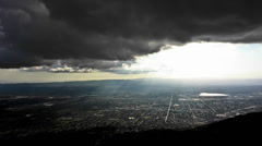 Time lapse of clouds passing dramatically over a city at sunset. Stock Footage