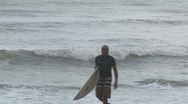 Stock Video Footage of Surfer walks beach carrying board