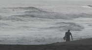 Stock Video Footage of surfer in silhouette strides along beach