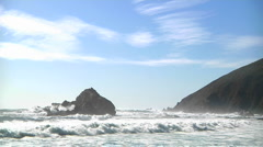 Waves roll into shore on a sunny day along California coastline. Stock Footage
