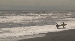 Two surfers contemplate waves Stock Footage