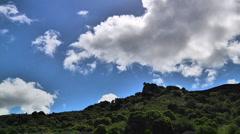 Viivästys pilvet kulkee yli vihreän vuorenrinteellä. Arkistovideo