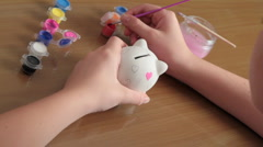 Girl paints pig-coin box. Stock Footage