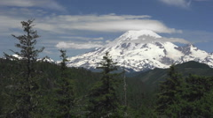 Time lapse of clouds passing a snow capped mountain surrounded by forest. - stock footage