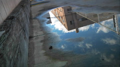 Time lapse of clouds passing over an urban building as reflected in a puddle on - stock footage