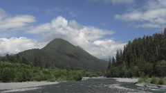 Time lapse of clouds passing over a forest, mountains and river. Stock Footage