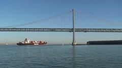 Ship passing by bay bridge San Francisco - stock footage