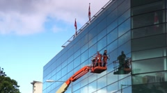 Workers standing on crane washing glass building with two flags on top Stock Footage