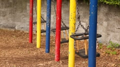 Side view on swings swaying in some lonely calm place Stock Footage