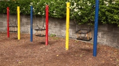 Three swings swaying on some play-field Stock Footage