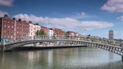 Busy people walking on Ha'penny Bridge across River Liffey in Dublin Stock Footage