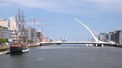 Old ship stay in front of contemporary Samuel Beckett Bridge in Dublin Stock Footage