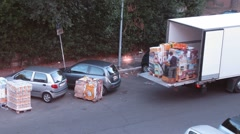 Two men load some cargo on truck with pallet jack  in Rome, Italy. Stock Footage