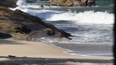 Waves break on rocky beach - stock footage