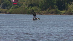 Man Standing To Row His Canoe Stock Footage