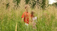 Boy and girl are working way through thick grass Stock Footage