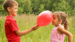 Boy and girl play with balloon in form of heart Stock Footage