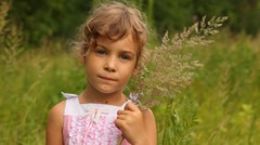 Girl is holding the blades of grass which she has gathered in field Stock Footage