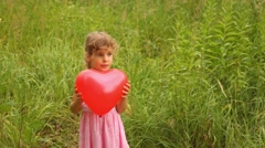 Girl is throwing up  an inflatable heart merrily Stock Footage