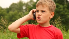 Boy is speaking on his mobile phone in the park Stock Footage