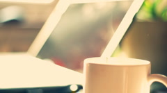 Steamy cup of coffee or tea with laptop in background Stock Footage