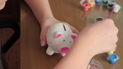 Girl paints pig-coin box. II. Stock Footage