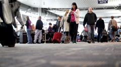 Airport terminal with lots of people carrying luggage Stock Footage