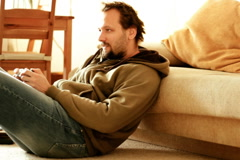 Man sitting on the floor and playing videogames  Stock Footage