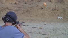 Young man fires small caliber rifle at target Stock Footage