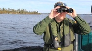 Stock Video Footage of Border Patrol Agent Scans with Binoculars (HD) co