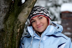 Happy woman standing by the tree in winter time Stock Footage