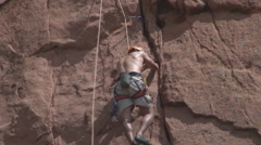 Climber wedges hands in cracks to lift himself Stock Footage
