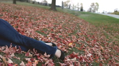 Young brunette laying in leaves on ground Stock Footage