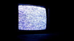 Static TV playing in dark with reflection on ground Stock Footage