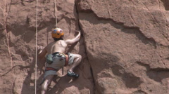 Muscles strain as rock climber stretches for lift Stock Footage