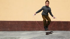 Boy jumping on skipping rope in yard Stock Footage