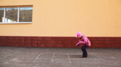 Boy and girl playing hopscotch jumping Stock Footage