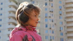 Girl standing in yard with headphones and listening music Stock Footage