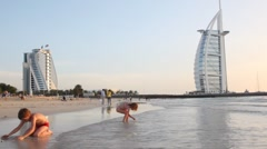 Kids playing on beach near Burj Al Arab five-star hotel during sunset Stock Footage