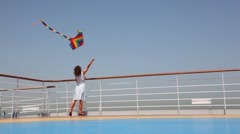 Back view on woman flying a kite on deck Stock Footage