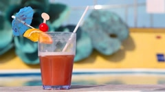 Glass of cocktail standing in foregroung in swimming pool Stock Footage