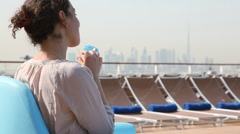 Back view on woman sitting on deck of ship and drinking cocktail Stock Footage